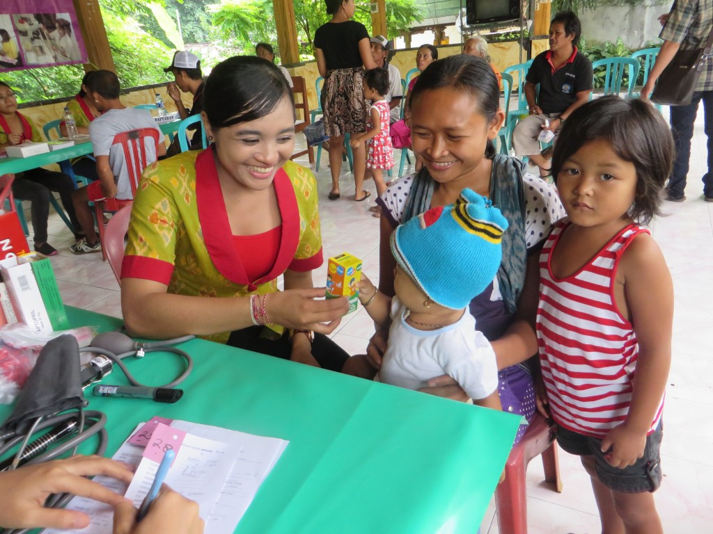 Mobile Clinic Coordinator Gung Ayu delivers nutritional support to parents and children in Bontihing Village.